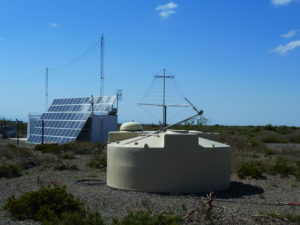 Water Cherenkov tank in front of an LPDA antenna and the central radio station.